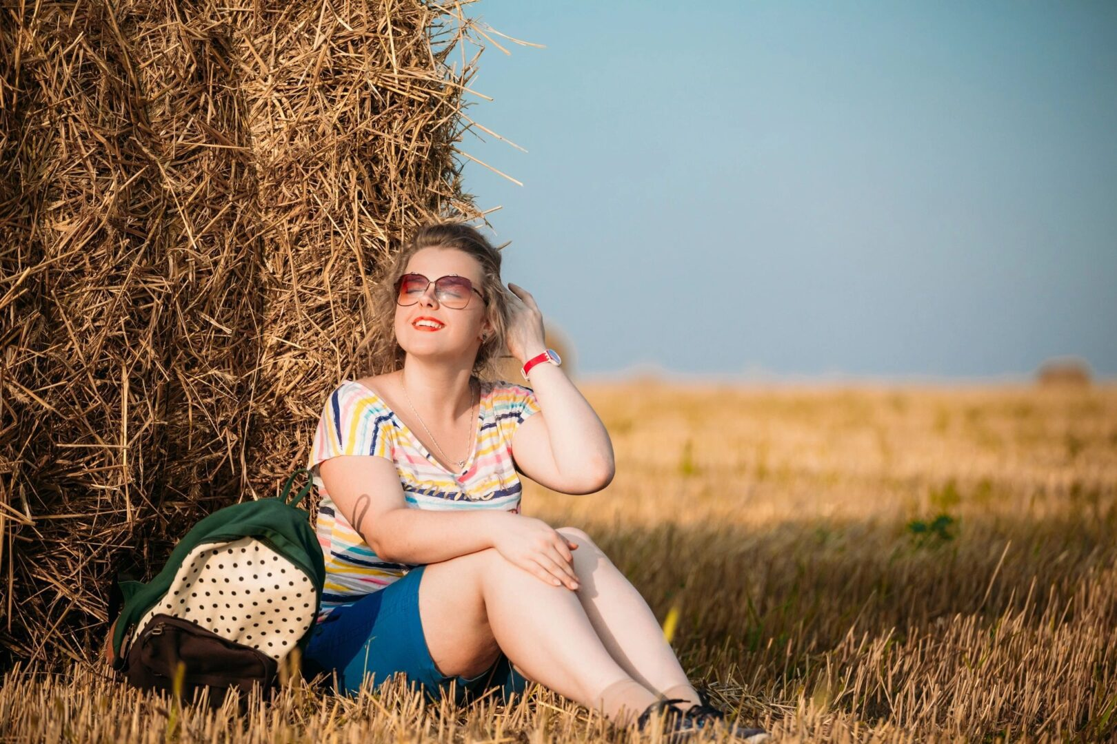 A woman sitting down and taking a picture next to hay