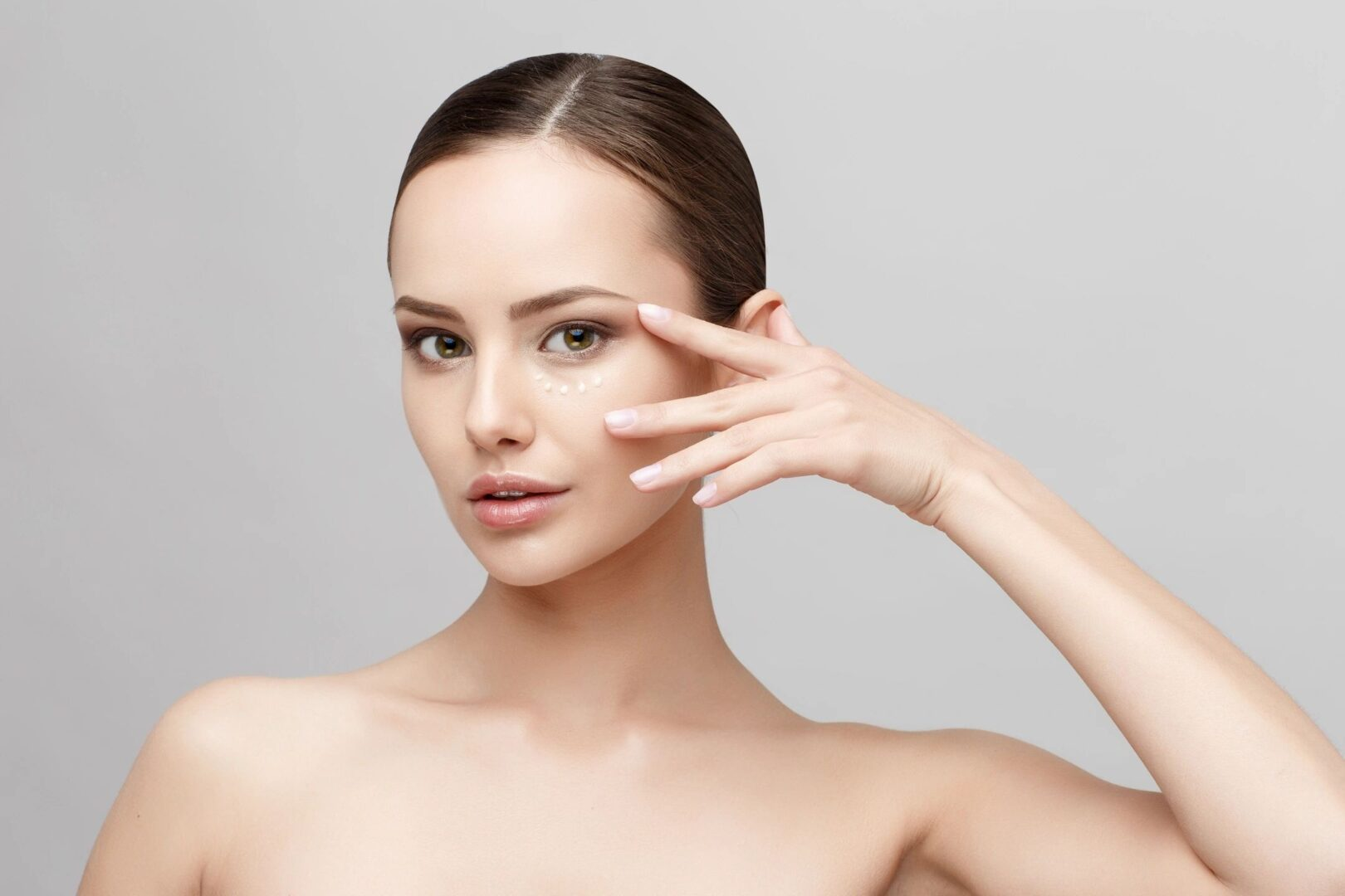 A woman putting skin care product on her face