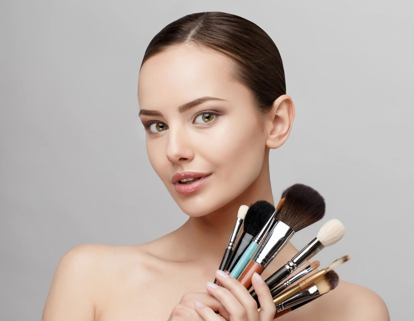 A woman holding a variety of make up brushes