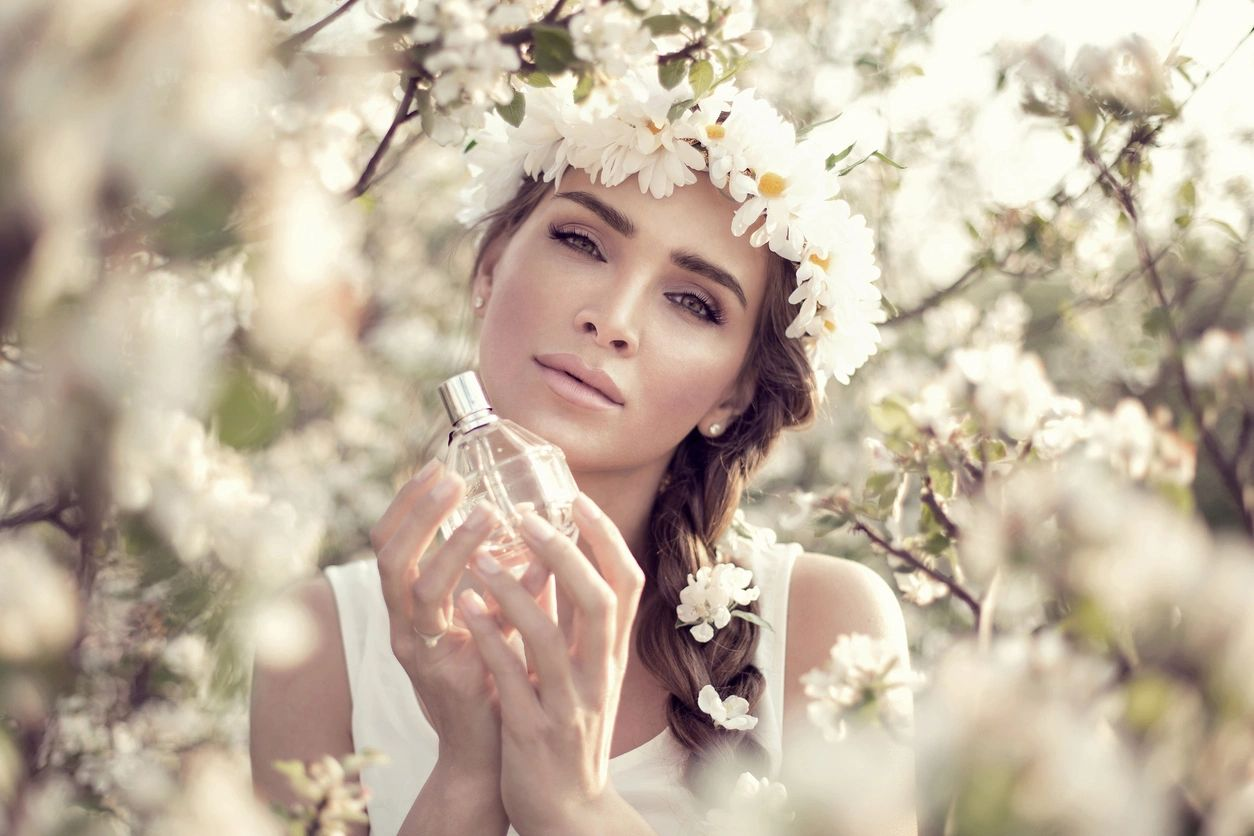 A woman wearing a flower crown and holding a perfume bottle