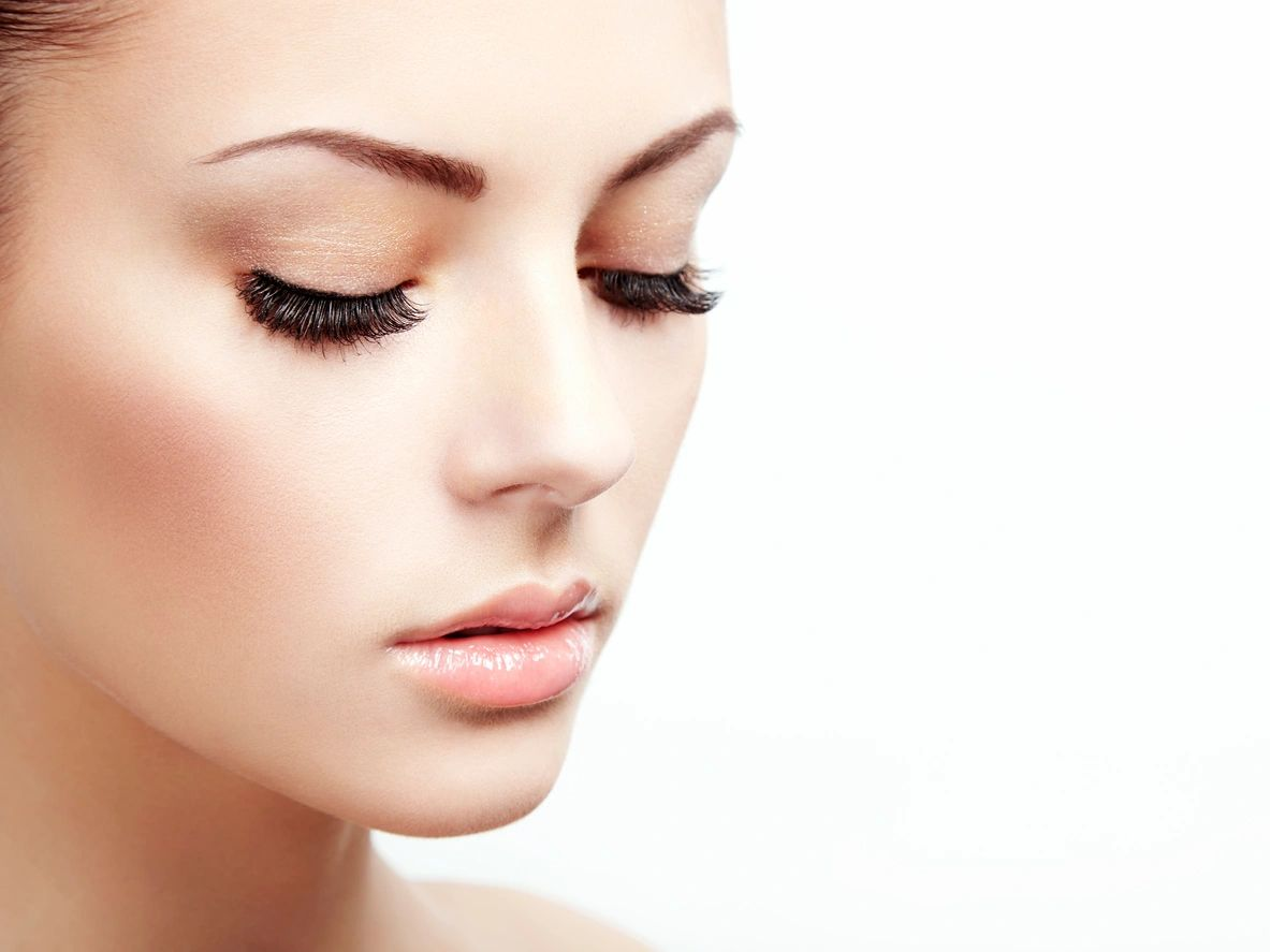A woman with thick eyelashes looking down
