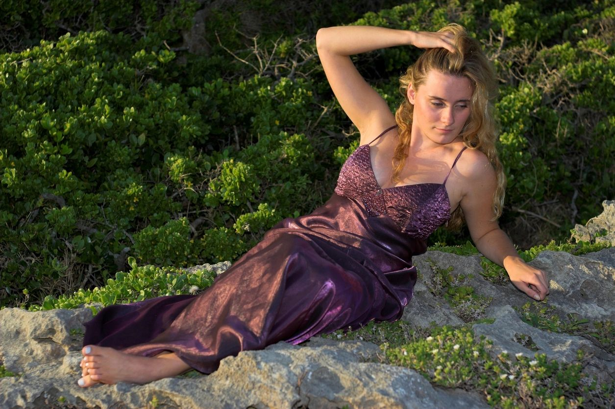 A woman wearing a gown and posing on top of a rock